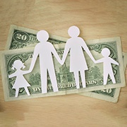 $20 bills underneath a paper cutout of a family of four