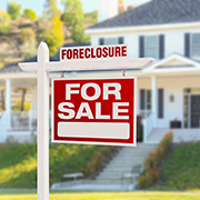 Foreclosure 'For Sale' sign in front of a house