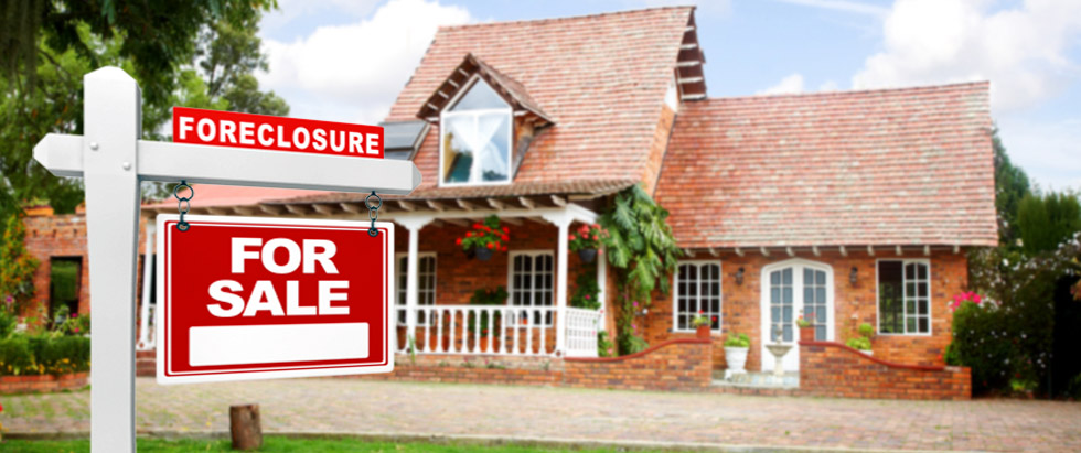 "Foreclosure ""For Sale"" sign appearing in front of a house"