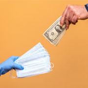 Two hands exchanging medical masks for dollar bills