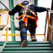 Worker going up stairs while wearing safety harnesses and ropes