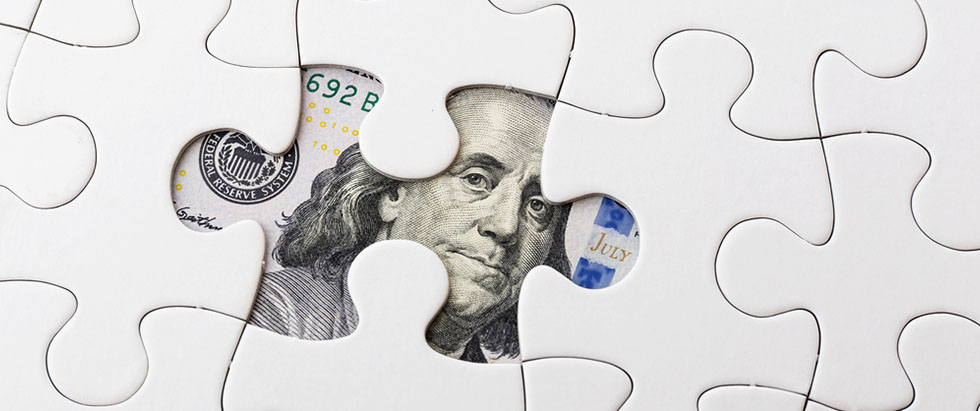Jigsaw puzzle with a $100 underneath it