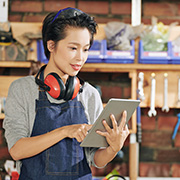 Employee wearing overalls and ear protection using a tablet at work