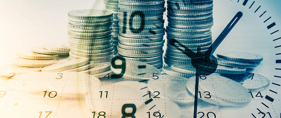 Clock face superimposed on top of stacks of coins and a calendar