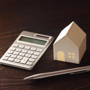 Small model house next to a calculator and pen