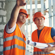 Two construction workers wearing hard hats and orange vests