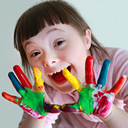 Young girl with different colors of paint on her hands to finger paint.
