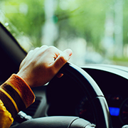 Person's hand on a car's steering wheel