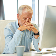 Tired business owner sitting in front of a computer screen