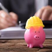 Pink piggy bank wearing a yellow hardhat