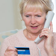 Elderly woman holding a credit card while talking on the phone