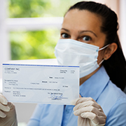Woman wearing a mask holding a check