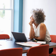 Woman sitting at a table in a conference room looking outside a window