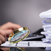 Person reviewing a document with a magnifying glass