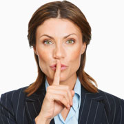 Woman holding a finger over her mouth - shushing