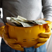 Yellow construction helmet full of cash