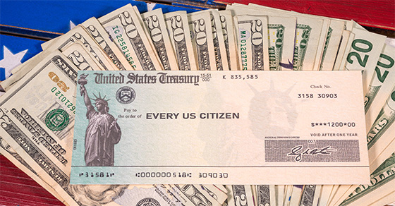 Stimulus check on top of cash and the American flag
