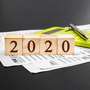 """2020"" blocks lying on top of 1040 tax form"