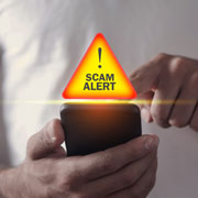"""man using a smartphone that has a """"scam alert"""" notification"""