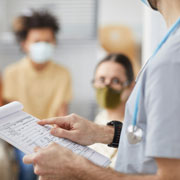 nurse with a clipboard in a room with people wearing masks