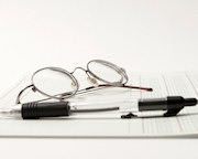 pen and glasses resting on top of a spreadsheet