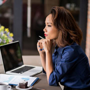 Businesswoman sitting in front of a laptop brainstorming