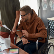 Man wearing a hooded sweatshirt sitting in a wheelchair