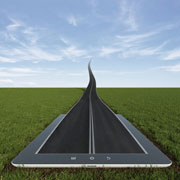 A road stretching out into the sky from a tablet lying in a grassy field