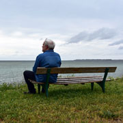 Elderly man sitting on a park bench looking out at the ocean