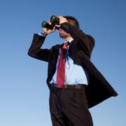 Businessman looking through a pair of binoculars