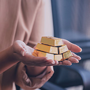Pair of hands holding small gold ingots