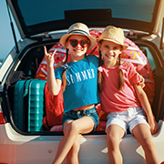 Children on vacation sitting on the bumper of their car