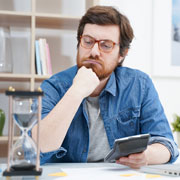 Man thinking while watching an hourglass