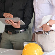 pair of construction professionals using a tablet