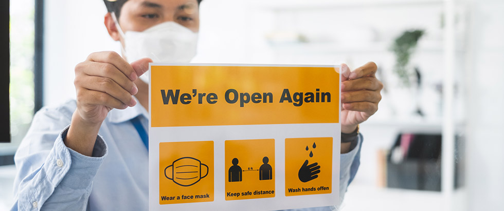 """Man posting a """"We're Open Again"""" sign"""