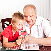 grandfather and grandson looking at a collection of coins
