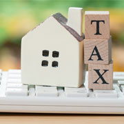 """Wooden blocks spelling """"Tax"""" leaning next to a small model house on top of a calculator"""