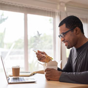 man eating noodles while sitting in front of his laptop
