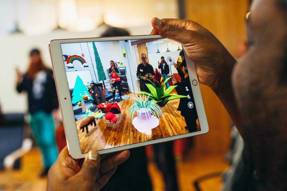 man viewing a collaborative AR scene through an iPad.