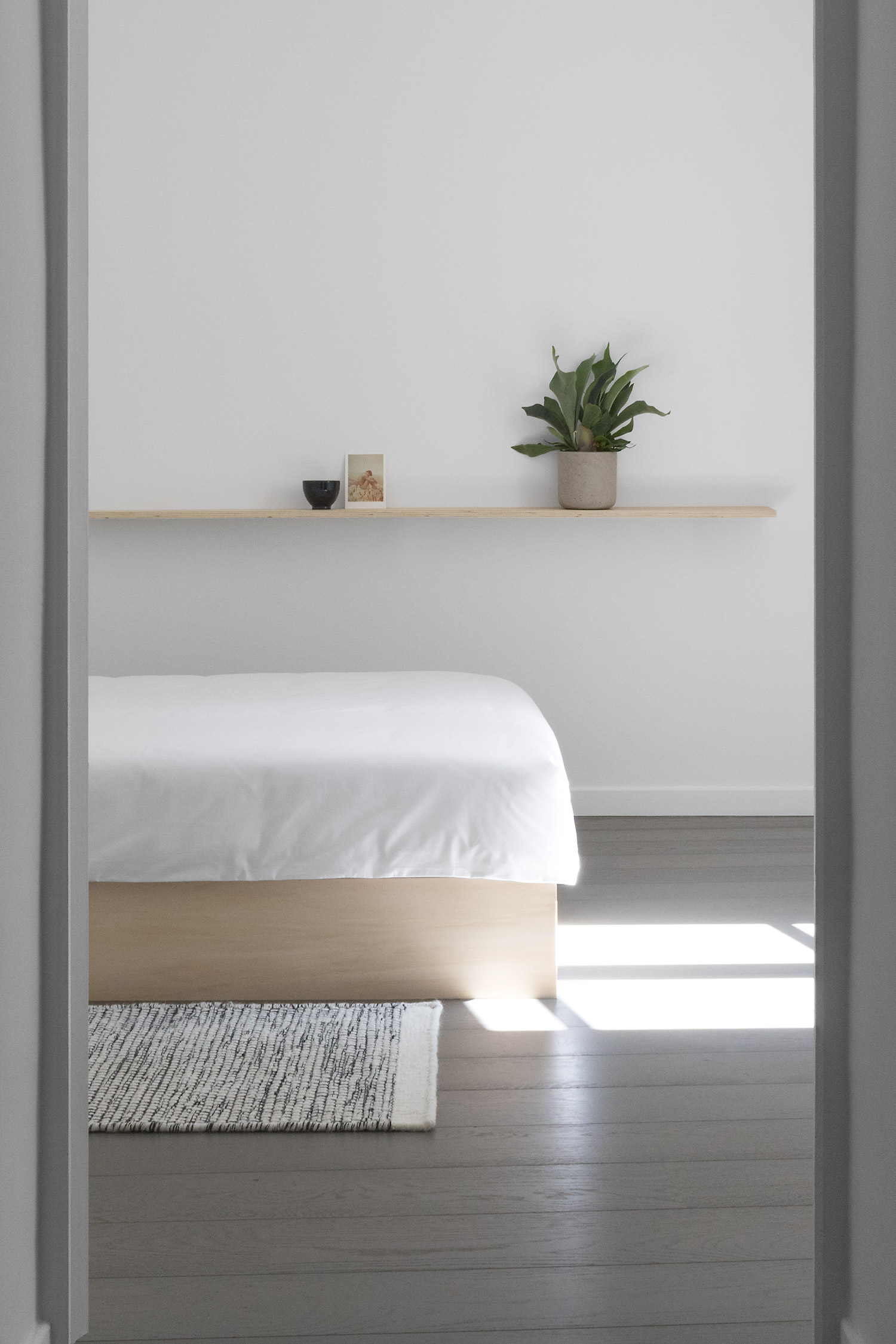 Doorway into minimal, modern Japanese style white tranquil bedroom with plywood bed plinth