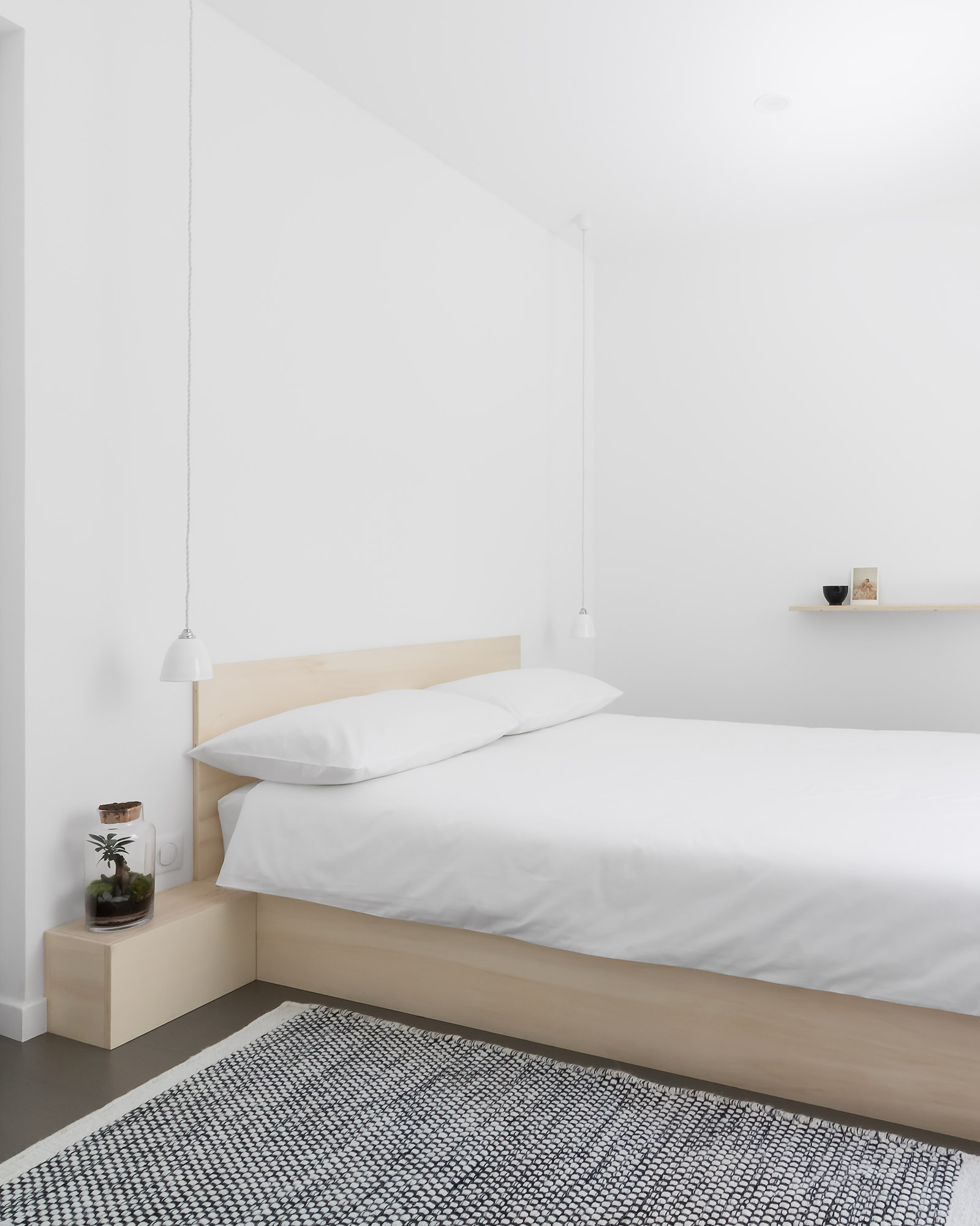 Minimal, modern Japanese style, white bedroom with low plywood bed and opaque glass pendant lights suspended on grey fabric cord