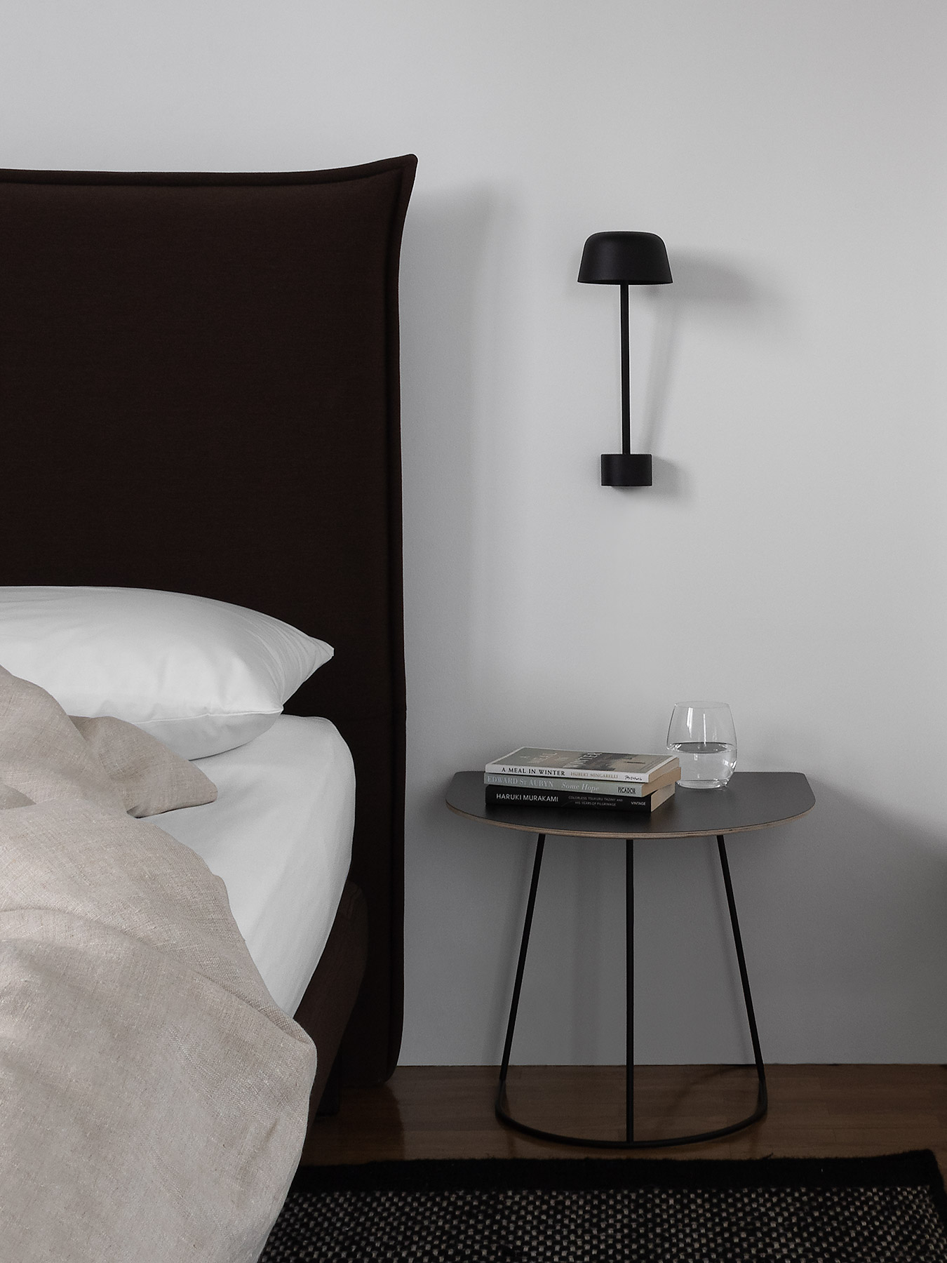 Bed with natural linen and contemporary dark brown headboard, modern black Scandinavian wall light and table, black rug