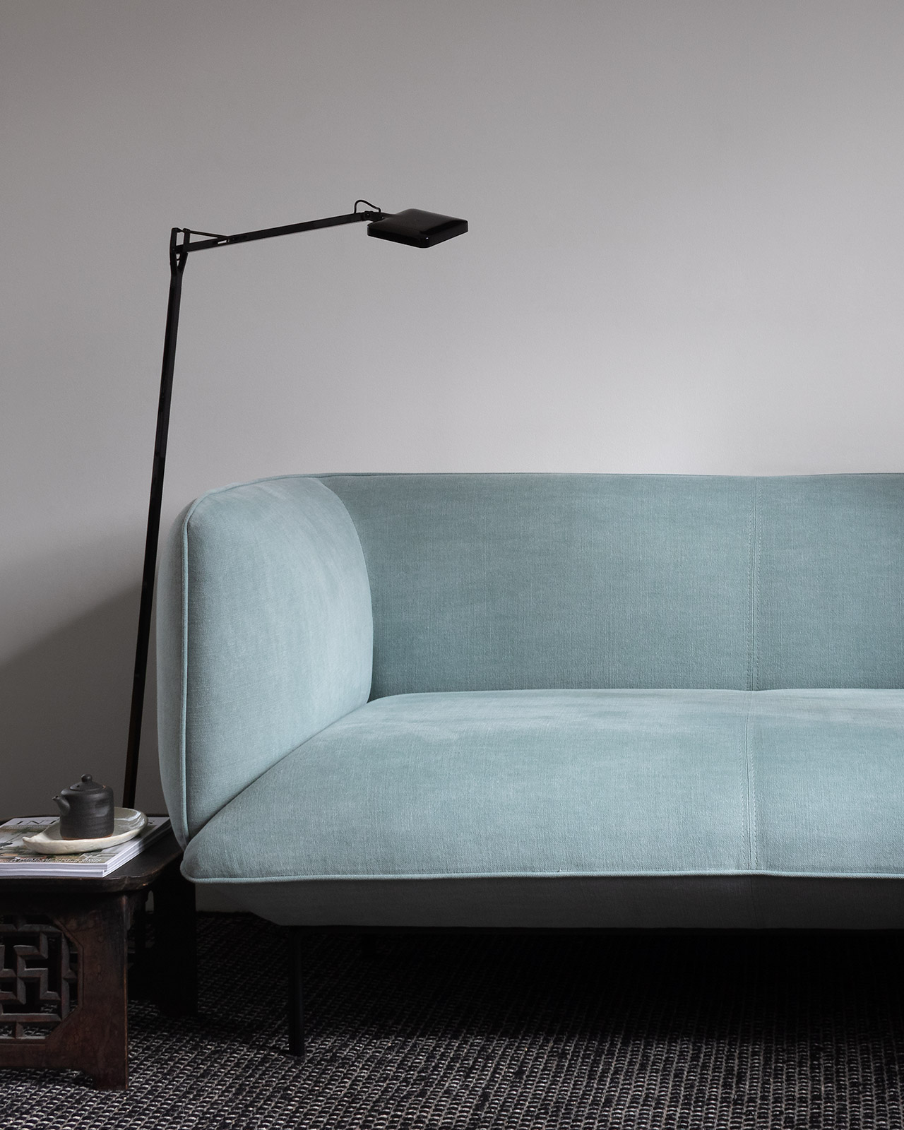 Teal Scandinavian sofa, black floor lamp and traditional Japanese tea table on black rug