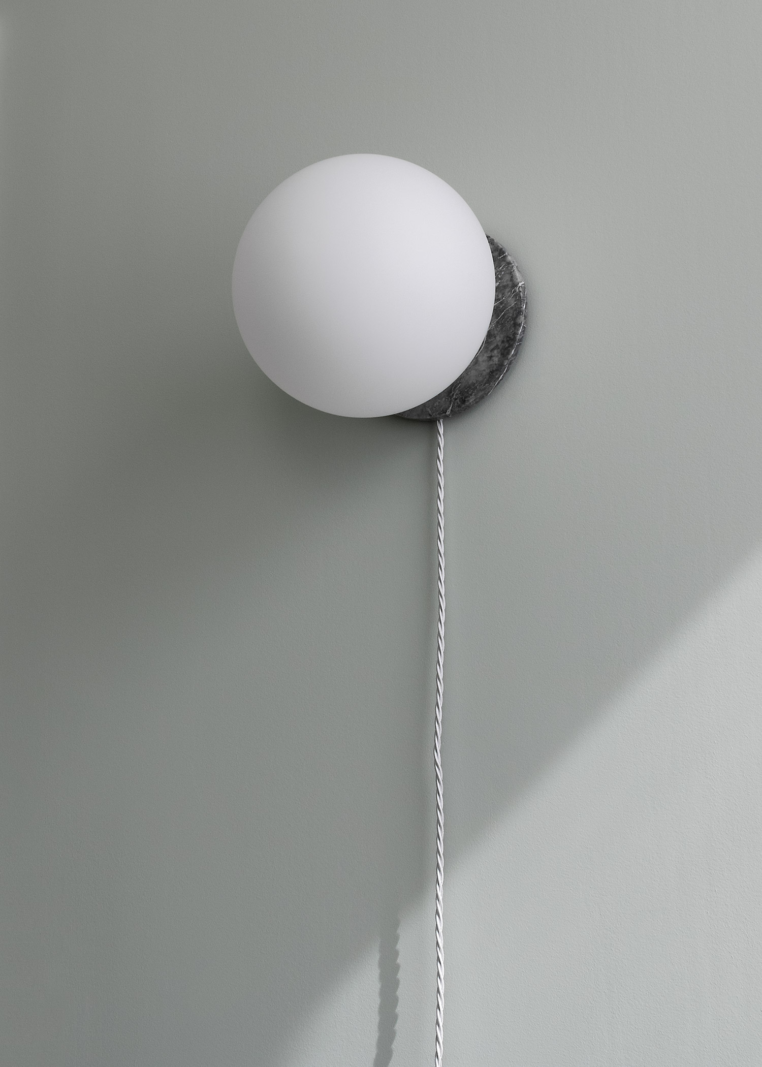 Wall light with grey marble base, white globe and fabric cord