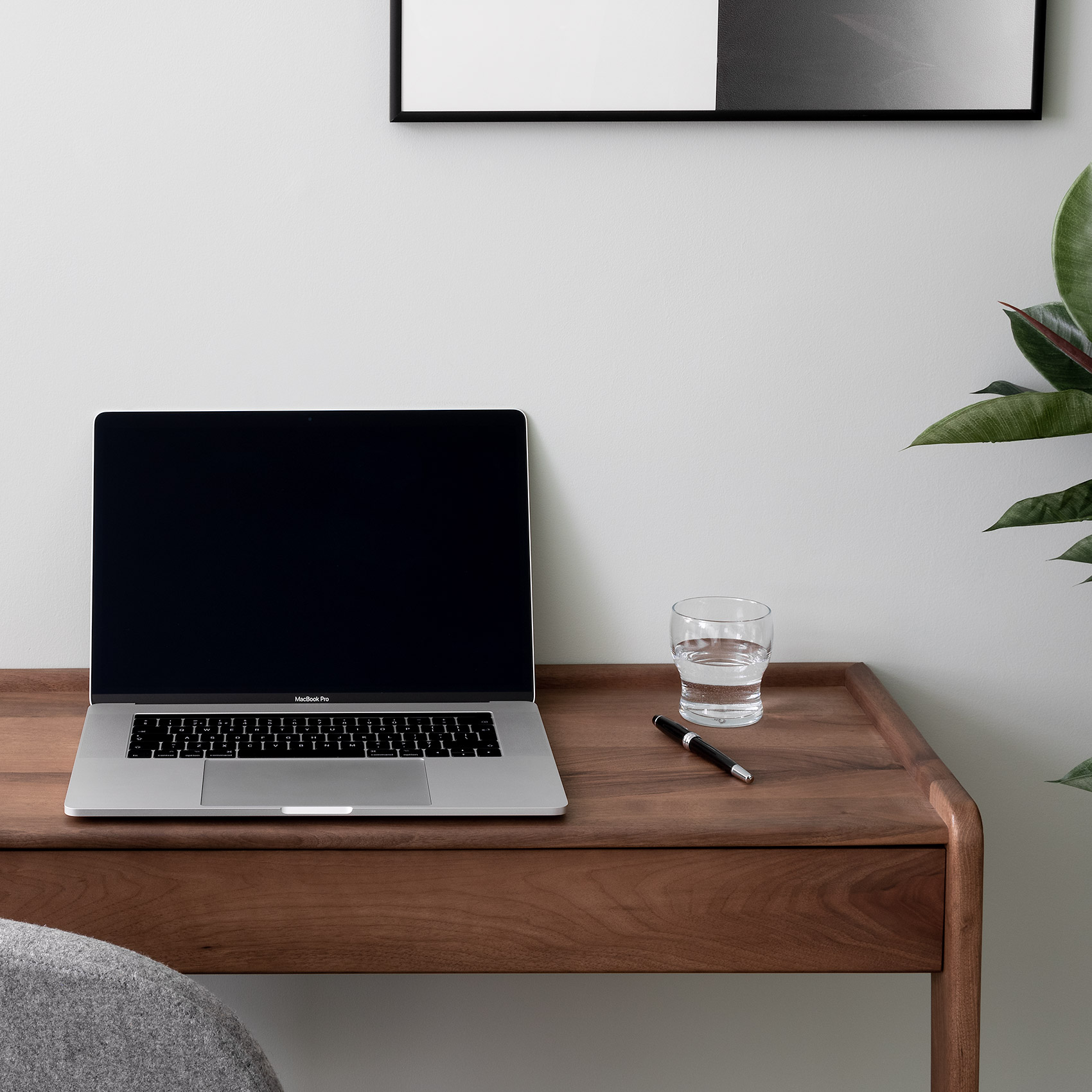 Walnut desk, macbook pro, grey wool chair and rubber plant