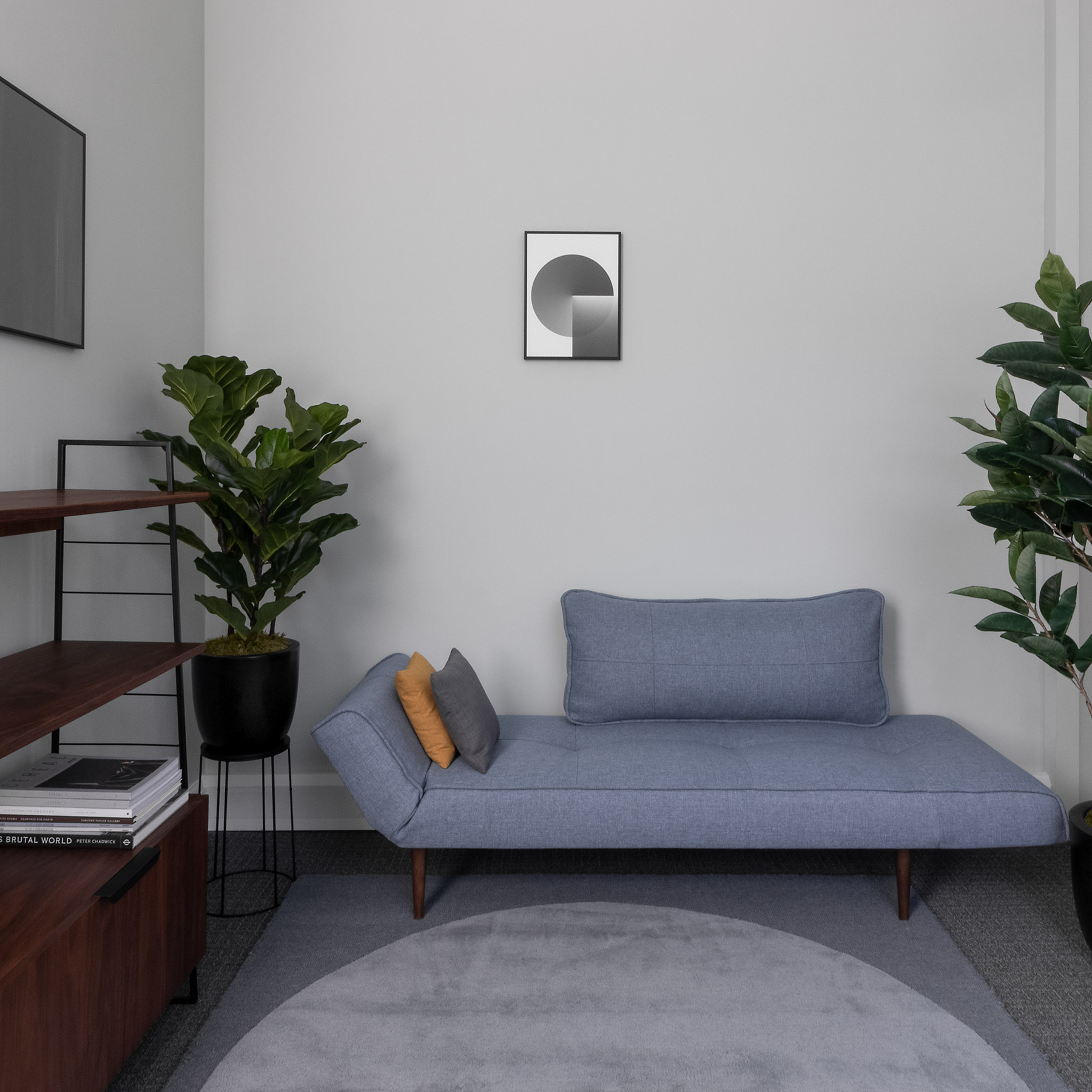 Psychotherapy room with sage grey walls, blue grey daybed, walnut cabinet, abstract geometric art and rug, ficus plant
