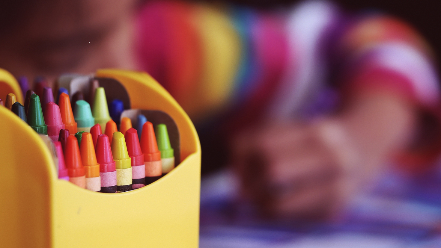 A preschool child coloring with a crayon