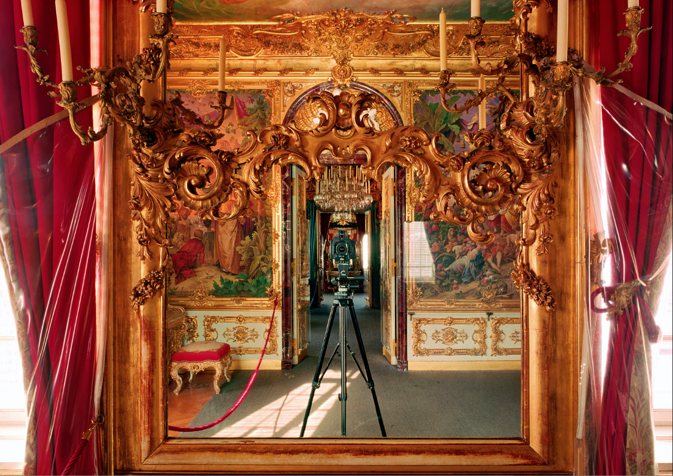 Die Photographien von Alexander Timtschenko sind Interpretationen vertrauter, bereits vielfach dargestellter und dokumentierter Welten, die sich längst in unserem kollektiven Gedächtnis befinden und unsere Wahrnehmung von Wirklichkeit beherrschen. Seine Bilder verwandeln moderne Metropolen in berauschende Farbarchitekturen. Szenarien in Palästen und Museen werden zu einer lebendigen Zeitreise. Und die kulissenhaften Kopien europäischer Baudenkmäler, etwa in Las Vegas, entsprechen auf seinen Aufnahmen exakt unserer idealisierten und stereotypen Vorstellung des Ortes und erscheinen uns gerade deshalb so real. In seiner aktuellen Ausstellung präsentiert Timtschenko in der Galerie REYGERS eine Bildserie, die sich mit den Innenräumen der Schlösser von König Ludwig II. auseinandersetzt. Die Kompositionen der Photoarbeiten, die angewandten Techniken der Langzeitbelichtung und der extremen Farbsättigung reflektieren dabei die Vorliebe des bayerischen Monarchen für Pracht und Opulenz. Die schemenhaften Gestalten der zeitgenössischen Besucher, die Reflexionen von Glas und Licht sowie die immer wieder abgebildete Kamera des Künstlers kreieren andererseits eine deutliche Zeitbezogenheit.