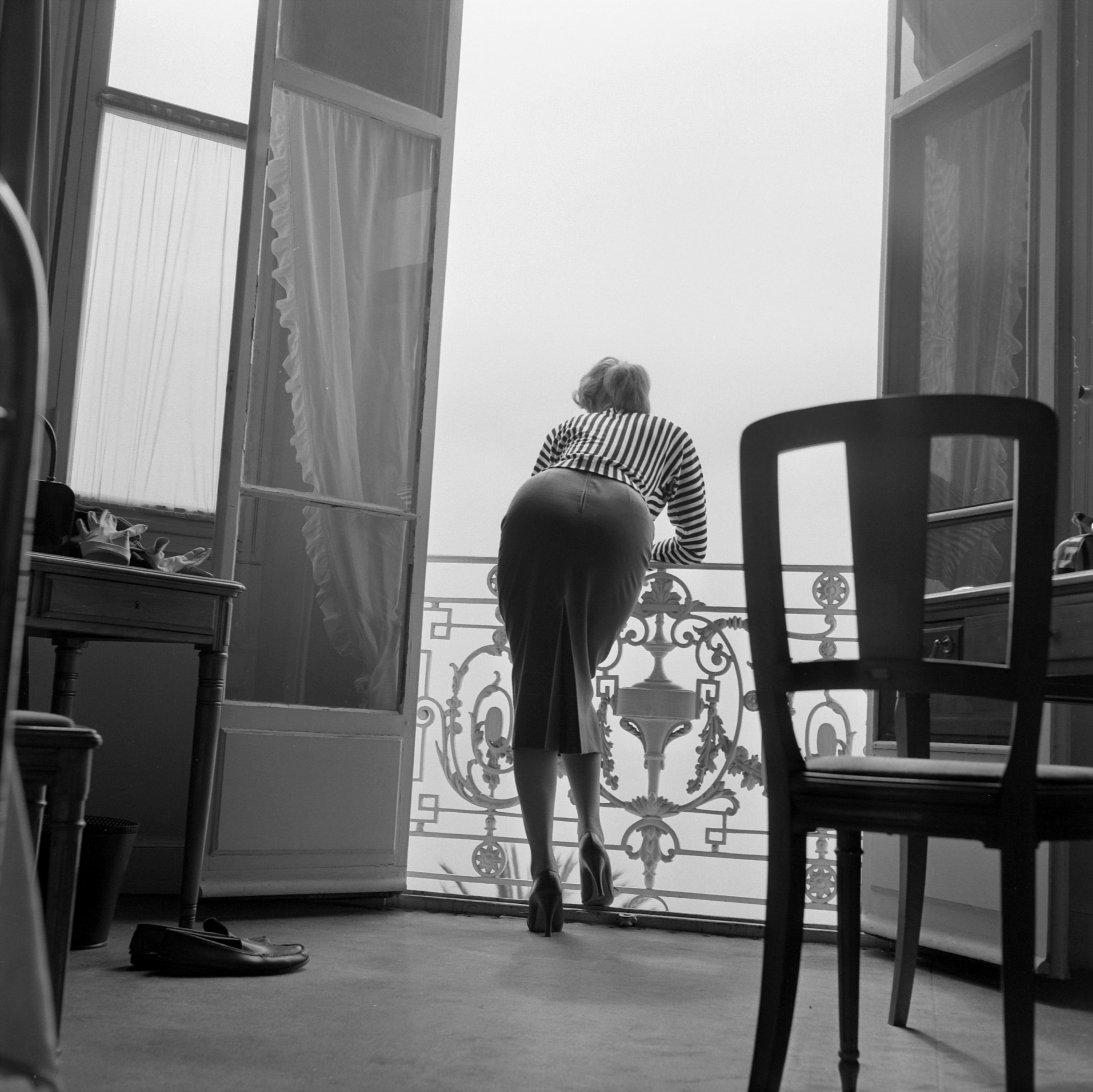 """Kein Fotograf hat das gesellschaftliche und kulturelle Leben an der Cóte d'Azur der """"Golden Fifties"""" so umfassend, hellwach und mit feiner Ironie dokumentiert wie der Ire Edward Quinn (1920-1997). Das Highlife auf Yachten, in Hotelsuiten und an Strandpromenaden, das Zusammentreffen von Stars, Managern, Aristokraten und Künstlern boten ein weites Terrain. Aus dieser Zeit stammen Quinns sensible Photos von """"Celebrities"""" wie Brigitte Bardot, Sophia Loren, Marlon Brando, Kirk Douglas, Gunther Sachs und so viele mehr. Die ersten Aufnahmen, die Gret Quinn in Zusammenarbeit mit ihrem Mann vergrößert, archiviert und an Illustrierte, Magazine, Agenturen und Zeitungen verschickt, gehören in den Bereich Pin-Up-Photographie. Die Posen der Girls können aus heutiger Sicht etwas unfreiwillig Komisches haben, gleichzeitig zeigen sie eine Art erotischer Unschuld, die sich aus den sozialen Normen der Zeit ergibt, aus der Spannung zwischen Alleszeigenwollen aber nicht Alleszeigendürfen. Spätere Stars begannen ihre Karriere an der Còte d'Azur als wenig bekannte Schauspielerinnen, wie z.B. Audrey Hepburn, die bereits früh von Quinn portraitiert wurde; aber auch die sehr junge Brigitte Bardot, die der Photograph einige Zeit unbefangen, leicht und authentisch abzubilden vermochte, bevor sie ihren eigenen Starphotographen hatte."""