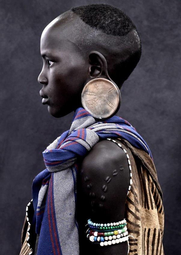 """Drei Tage dauert die Fahrt von Addis Abeba Richtung Süden. Ziel ist das Omo-Tal in Äthiopien nahe der Grenze zu Kenia und dem Sudan. Eine mühsame Reise über tausend Kilometer. Das Fahrzeug rumpelt über Schotterpisten und wird immer wieder von Vieh aufgehalten, das auf der Straße entlang trottet. Langsam nähert sich der Fotograf Mario Marino einer anderen Welt. Gemeinsam mit seinem Fahrer und Übersetzer Alex lässt er das an Plastikmüll erstickende, von westlichen T-Shirts dominierte Afrika hinter sich. Hier findet der Fotograf was er gesucht hat: die kulturellen Wurzeln des Landes. Marino möchte Portraits machen, von Menschen, die es so wahrscheinlich in einigen Jahren nicht mehr geben wird. Monate der Recherche gingen dieser Reise voraus. Doch trotzdem ist jetzt alles unbekannt und unwägbar – so bleibt Marino nur übrig, sich von Tag zu Tag auf das Neue und Überraschende ein zu lassen: """"Jeden Morgen stand ich auf und alles war offen. Welche Menschen ich treffe und wie sie reagieren würden, konnte ich nur erahnen."""" Seine Motive sucht er in den kommenden zwei Wochen täglich in einem anderen Dorf, bei einem anderen Stamm. Er findet die Menschen auf der Straße und auf Marktplätzen und positioniert sie vor seinem neutralen Hintergrund, um sie aus ihrem sozialen Umfeld zu lösen. Im Nu drängt sich um das mobile """"Studio"""" eine Menschentraube. Die einzige Lichtquelle ist das strahlende Tageslicht. Mit schnellen Handgriffen kommen einfache fotografische Hilfsmittel zum Einsatz. Marino portraitiert die Menschen in ihrem alltäglichen Habitus – genauso wie er sie entdeckt. Wenige Momente genügen, um eine bestechende Eindringlichkeit der Porträts zu erreichen. Er nennt seine Arbeiten """"fotografische Psychogramme"""". Mario Marino macht keine Fotoreportage, keine Dokumentation eines fremden Alltags. Was bei ihm entsteht, ist das zeitlose Porträt eines Individuums, ein fotografischer Fingerabdruck, der tief in die Seele des Portraitierten blicken lässt und dabei viel über dessen kulturel"""